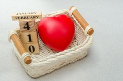 14 de febrero, el calendario de madera y el corazón rojo forman en cesta con Foto de archivo libre de regalías