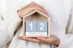 12 de febrero en el calendario la muchacha está sosteniendo un calendario de madera Día internacional de agencias de la boda, día Imagenes de archivo