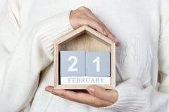 21 de febrero en el calendario la muchacha está sosteniendo un calendario de madera Día internacional de la lengua de madre, guía Fotografía de archivo