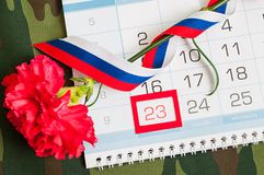 23 de febrero tarjeta Clavel rojo, bandera rusa y calendario con fecha el 23 de febrero enmarcado en la tela del camuflaje Foto de archivo libre de regalías