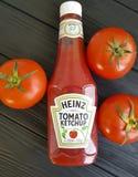 4 de febrero de 2017 Ucrania Kiev Heinz, botellas de salsa de tomate en tomates de madera negros foto de archivo libre de regalías