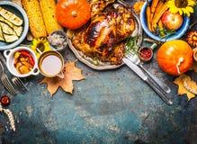 De feestelijke achtergrond van het Thanksgiving dayvoedsel met geroosterde gehele Turkije of kip en saus, oogstgroenten Royalty-vrije Stock Foto