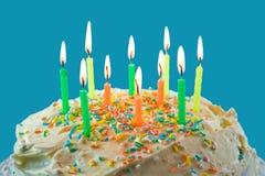 De feestelijke cake met aangestoken kaarsen en bestrooit. Stock Afbeelding