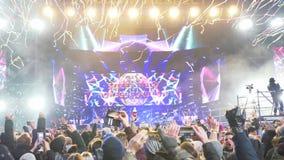 De feestelijke emoties, menigte van mensen schieten op mobiele telefoon de digitale aftelprocedure bij stadium de schermen en het stock videobeelden