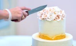 De feestelijke huwelijkscake met bloemen, geeloranje bloemen, zacht stapelbed, mooi, de bruid snijdt de cake royalty-vrije stock afbeeldingen