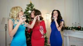 De feestelijke partij ter ere van het Nieuwjaar, gasten, mooie meisjesbespreking, lach, drinkt wijn van glazen op de achtergrond stock videobeelden