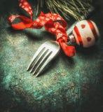De feestelijke plaats die van de Kerstmislijst met vork, lint, bal en pijnboom op donkere rustieke uitstekende achtergrond plaats Stock Afbeeldingen