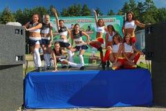De feestelijke prestaties van jonge mooie meisjes van het cheerleading van atleten steunen groepsduizeligheid (duizeligheid) Stock Afbeeldingen