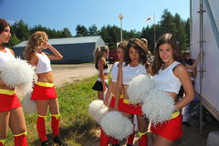 De feestelijke prestaties van jonge mooie meisjes van het cheerleading van atleten steunen groepsduizeligheid (duizeligheid) Royalty-vrije Stock Fotografie