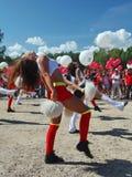 De feestelijke prestaties van jonge mooie meisjes van het cheerleading van atleten steunen groepsduizeligheid (duizeligheid) Royalty-vrije Stock Foto's