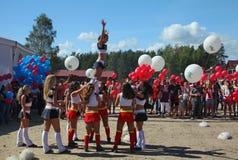 De feestelijke prestaties van jonge mooie meisjes van het cheerleading van atleten steunen groepsduizeligheid (duizeligheid) Stock Afbeelding