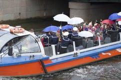 De feestelijke pretgebeurtenis over de watertram met gekostumeerde mensen kleedde zich colorfully en met paraplu's stock foto