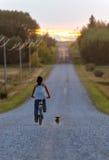 De ferme de fille de vélos route vers le bas avec le chien Image stock