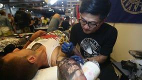 De festivaldeelnemer maakt tatoegeringen bij de 11de Internationale Tatoegeringsovereenkomst stock footage