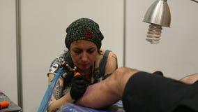 De festivaldeelnemer maakt tatoegeringen bij de 11de Internationale Tatoegeringsovereenkomst stock video