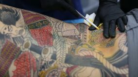 De festivaldeelnemer maakt tatoegeringen bij de 11de Internationale Tatoegeringsovereenkomst stock videobeelden