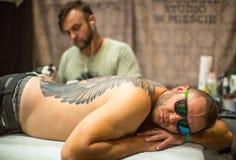 De festivaldeelnemer maakt tatoegeringen bij de 11de Internationale Tatoegeringsovereenkomst in het Centrum congres-Expo van Krak Royalty-vrije Stock Foto's