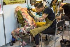 De festivaldeelnemer maakt tatoegeringen bij de 11de Internationale Tatoegeringsovereenkomst in het Centrum congres-Expo van Krak Royalty-vrije Stock Foto