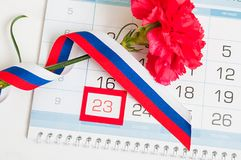 23 de fevereiro - defensor do cartão do dia da pátria Cravo, bandeira do russo e calendário vermelhos com data o 23 de fevereiro  Fotografia de Stock