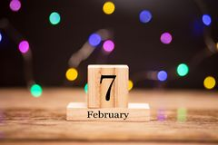 7 de fevereiro Dia 7 do grupo do mês de fevereiro no calendário de madeira no centro do fundo escuro com bokeh da festão imagem de stock