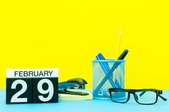 29 de fevereiro Dia 29 do mês de fevereiro, calendário no fundo amarelo com materiais de escritório Tempo de inverno, pulo-ano Imagens de Stock
