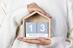 13 de fevereiro no calendário a menina está guardando um calendário de madeira Dia de rádio do mundo Imagem de Stock