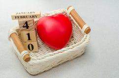 14 de fevereiro, o calendário de madeira e o coração vermelho dão forma na cesta com Foto de Stock Royalty Free