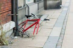 De fiets blijft aan een rioolbuis op een verlaten straat wordt gebonden die stock afbeelding
