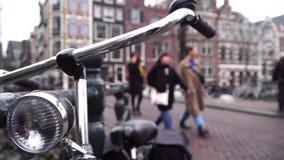 De fiets is in dichte omhooggaand van Amsterdam In de achtergrondmensengang rond de stad stock video