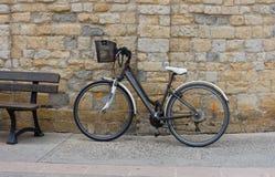 De fiets met een Zwarte metaalmand propped tegen een steenmuur Royalty-vrije Stock Foto