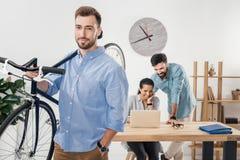 De fiets van de zakenmanholding terwijl collega's die aan laptop in bureau werken Stock Afbeelding