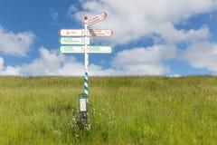 De fiets voorziet in gras met blauwe hemel van wegwijzers Stock Afbeeldingen
