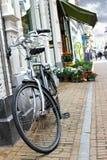 De fiets wordt geparkeerd dichtbij bloemwinkel Stock Afbeeldingen