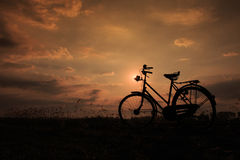 De fiets zette bij houten omheining in zonsopgang op Stock Afbeeldingen