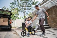 De fietsduw van de jonge geitjesrit door zijn vader royalty-vrije stock foto