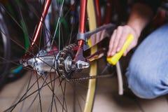 De fietsen van de themareparatie Het close-up van een Kaukasische mensen` s hand gebruikt een Kettingssmeermiddel in een geel sme stock afbeelding