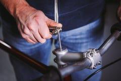 De fietsen van de themareparatie Het close-up van een Kaukasische mensen` s hand gebruikt een sleutel van de werktuighexuitdraai  royalty-vrije stock afbeelding