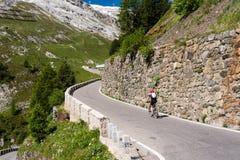 De fietser berijdt kronkelige bergweg in de alpen van Tirol Royalty-vrije Stock Foto's