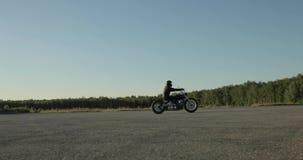 De fietser berijdt snel een motorfiets op de weg dichtbij het bos bij zonsondergang, zijaanzicht stock video
