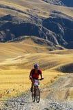 De fietser die van de berg in woestijn rent royalty-vrije stock foto