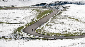 De fietser gaat bergaf langs een bergweg in een sneeuwlandschap Stock Foto's