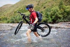 De fietser gaat over de doorwaadbare plaats van de bergrivier Royalty-vrije Stock Fotografie