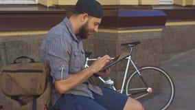 De fietser gebruikt tablet op de straat stock footage