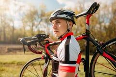 De fietser houdt de fiets op schouder, cirkelend sport stock foto