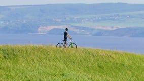 De fietser kijkt rond en beweegt zich neer van de groene heuvel stock videobeelden