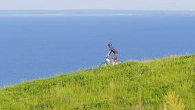 De fietser kijkt rond en beweegt zich neer van de groene heuvel stock video