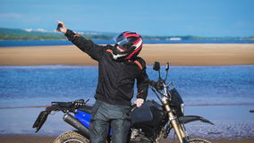 De fietser op de bank van de rivier, naast zijn motorfiets, maakt de foto op de telefoon