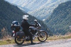 De fietser is op zijn avonturenmotorfiets aanwezig, de hoogste berg op achtergrond, enduro, van weg, mooie mening, gevaarsweg stock foto's