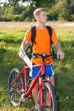 De fietser van de mens met fiets en kaart ter beschikking Stock Foto's