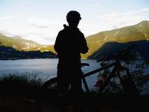 De fietser van de silhouetberg Stock Foto's